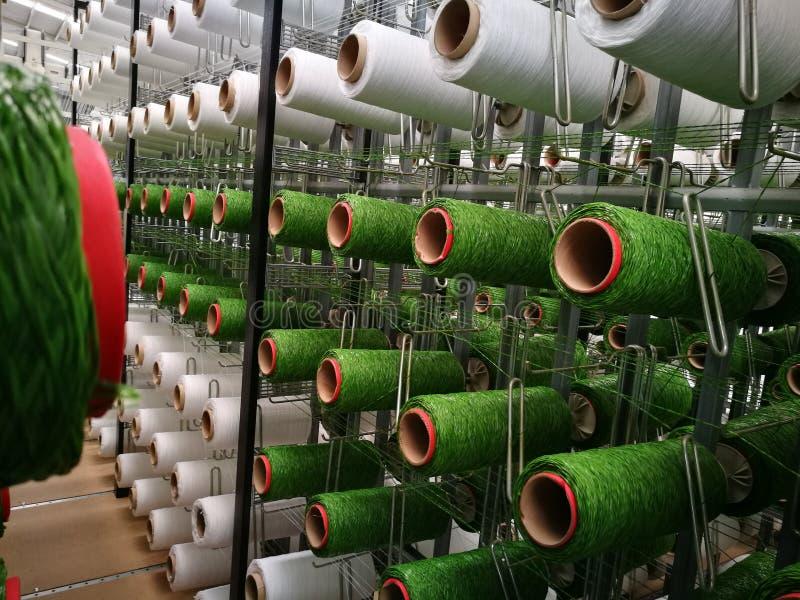 Hilados blancos y verdes en los estantes para los telares de la hierba artificial imágenes de archivo libres de regalías