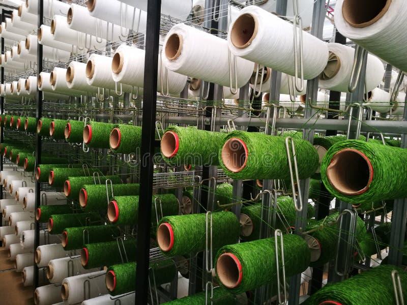 Hilados blancos y verdes en los estantes para los telares de la hierba artificial fotografía de archivo