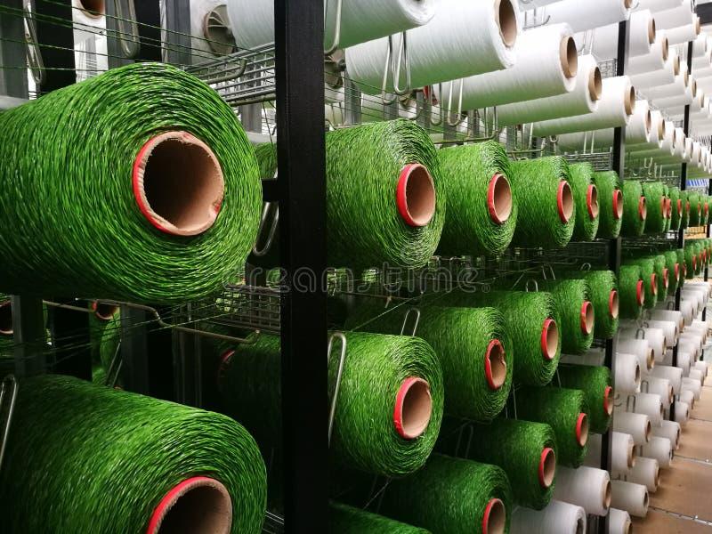 Hilados blancos y verdes en los estantes para los telares de la hierba artificial foto de archivo libre de regalías