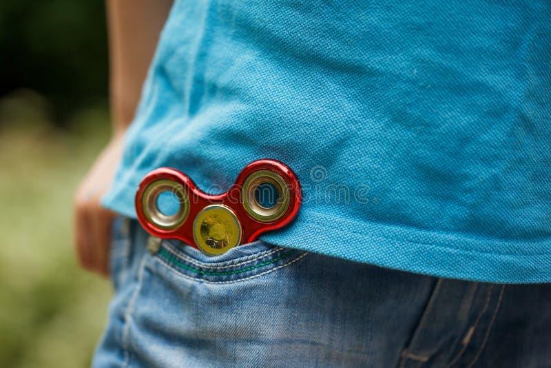 Hilandero de la mano de la persona agitada en fondo del bolsillo de los tejanos Juguete de moda y popular para los niños y el adu fotografía de archivo libre de regalías
