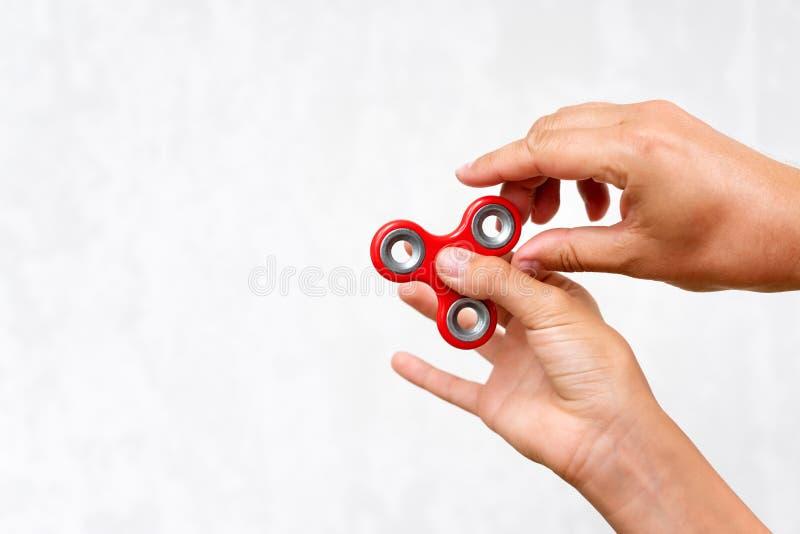 Hilandero de la persona agitada El hilandero rojo de la mano, muchachos que juegan con la mano que inquieta juega Alivio de tensi fotografía de archivo