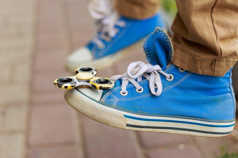 Hilandero de la persona agitada en la puntera de una zapatilla de deporte Juego, juguetes de moda, en imagen de archivo libre de regalías