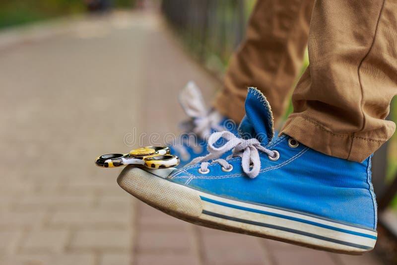 Hilandero de la persona agitada en la puntera de una zapatilla de deporte Juego, juguetes de moda, en imagenes de archivo