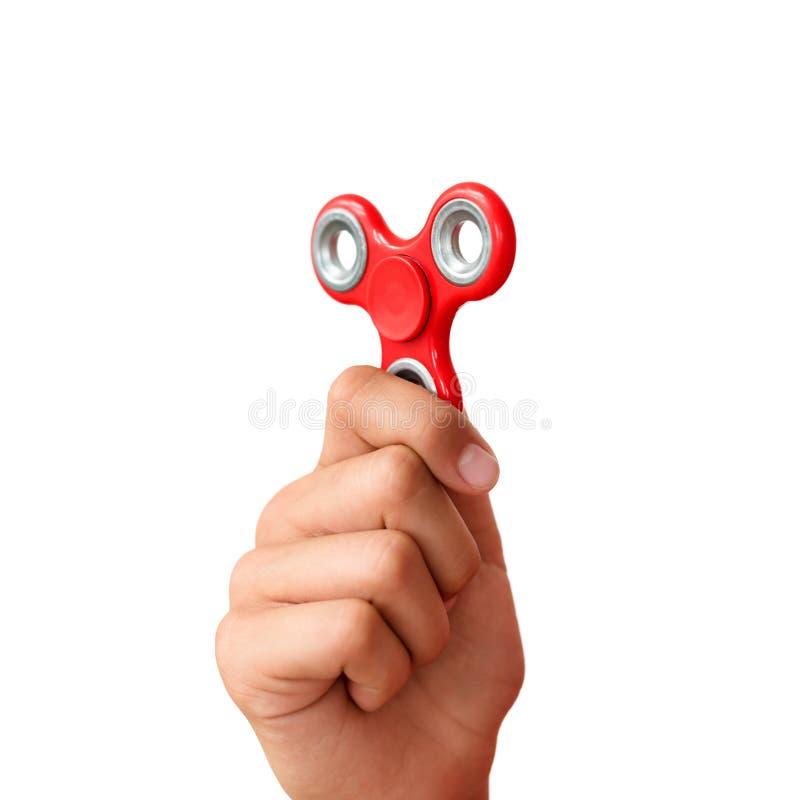 Hilandero rojo de la mano Muchacho que juega a un hilandero popular de la persona agitada del juguete en su mano Alivio de tensió foto de archivo