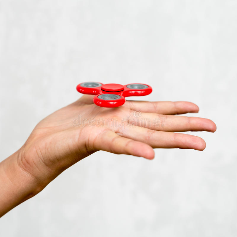 Hilandero rojo de la mano Muchacho que juega a un hilandero popular de la persona agitada del juguete en su mano Alivio de tensió imagen de archivo