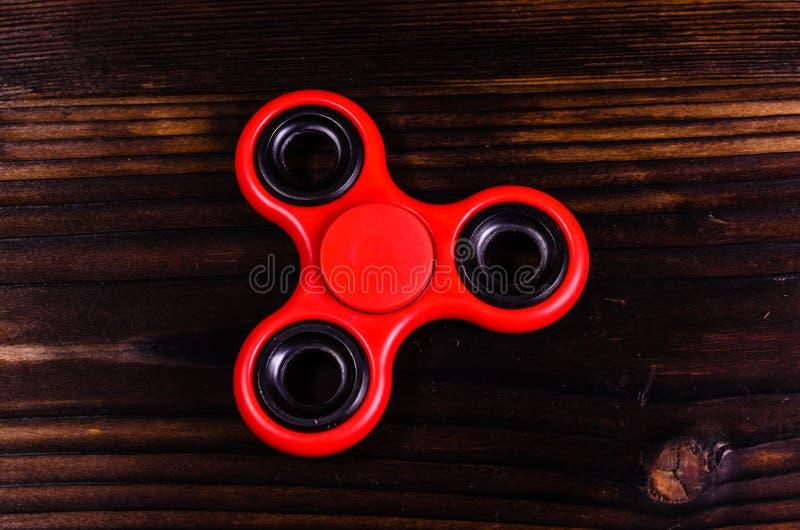 Hilandero rojo de la persona agitada en el escritorio de madera Visión superior fotografía de archivo libre de regalías