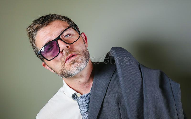 Hilarious portrait of 40s weird and wasted businessman in suit and tie wearing ridiculous big broken nerdy glasses posing royalty free stock photos