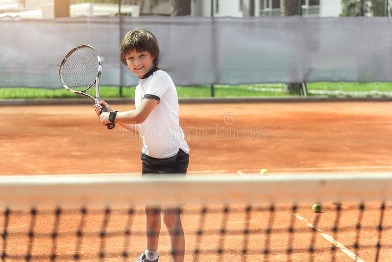 Hilarious smiling boy using racquet royalty free stock images