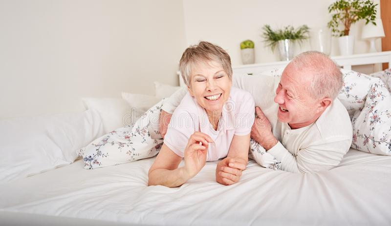 Hilariuos happy seniors having fun. And playing around in bedroom royalty free stock image