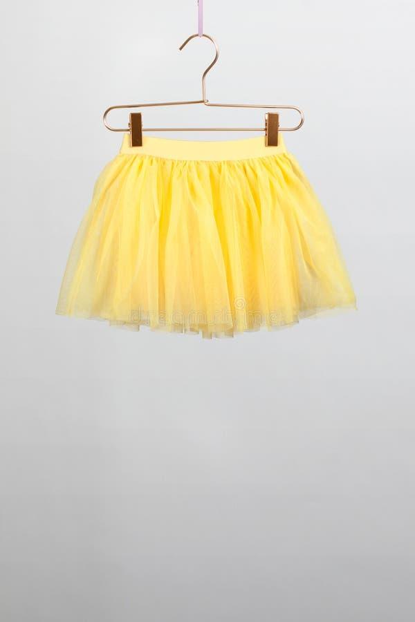 hildren在灰色背景的裙子黄色挂衣架 库存照片