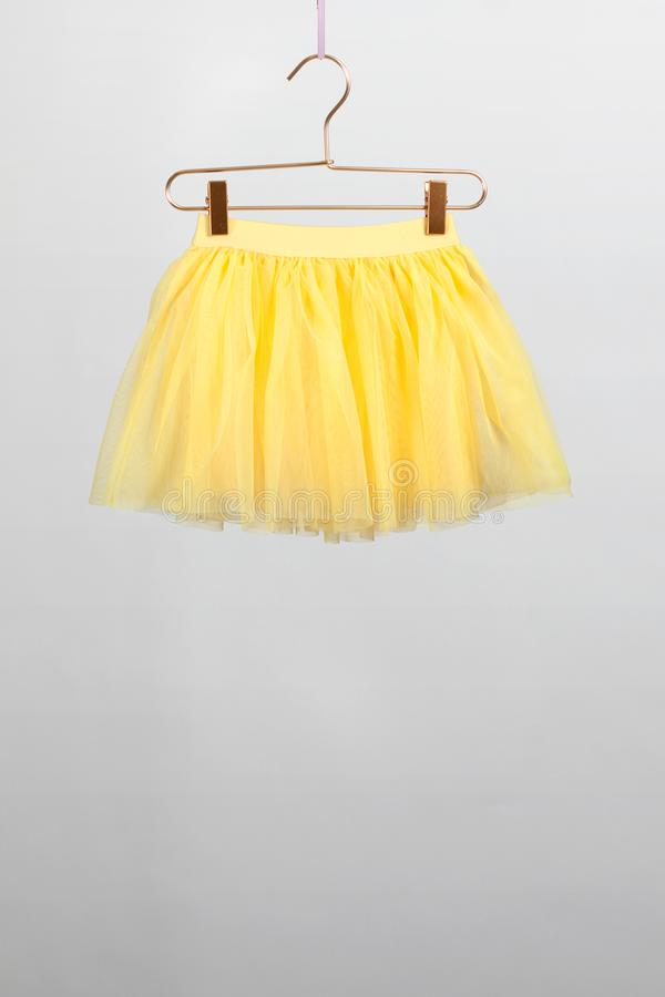 hildren le cintre jaune de jupe sur le fond gris photos stock