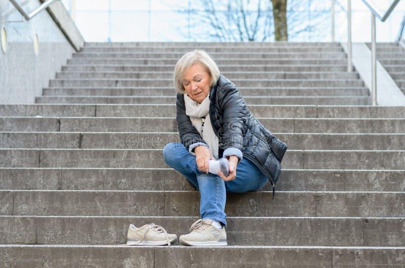 Hilflose ältere Frau, die ihren Fuß massiert stockbild