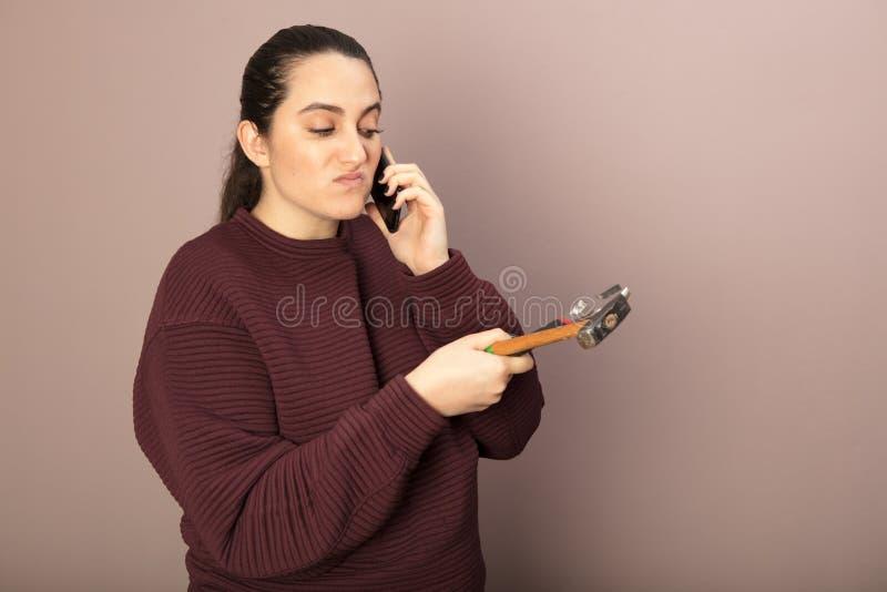 Hilflose Frauenholdingwerkzeuge, die am Telefon sprechen stockfotos