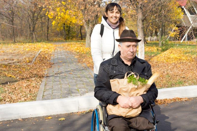 Hilfreiche Frau, die einen älteren Mann in einem Rollstuhl drückt lizenzfreie stockfotos