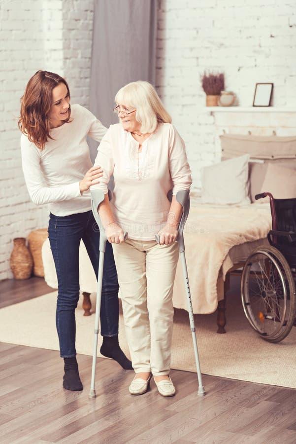 Hilfreiche junge Frau, die zu Hause arbeitsunfähiger alter Mutter hilft lizenzfreie stockfotografie