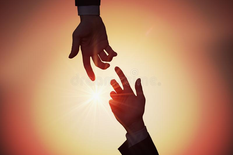 Hilfs- und Unterstützungskonzept Zwei Hände erreichen sich bei Sonnenuntergang stockfotos