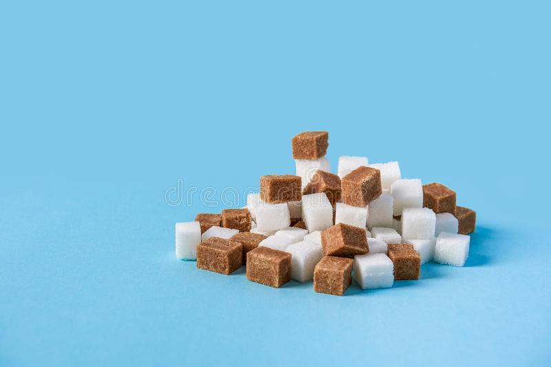 Hill φιαγμένο από άσπρους και καφετιούς κύβους ζάχαρης που απομονώνονται στο μπλε υπόβαθρο στοκ εικόνα με δικαίωμα ελεύθερης χρήσης