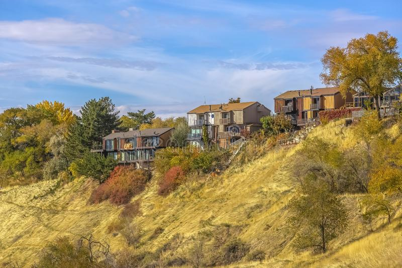 Hill with homes and colorful trees under vast sky. Beautiful view of a hill in Salt Lake City, Utah with colorful trees and plants. Homes are on top of the royalty free stock photos