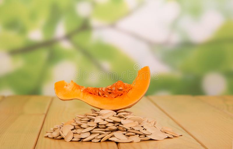 Hill of pumpkin seeds and slice of pumpkin on top of an abstract green stock image