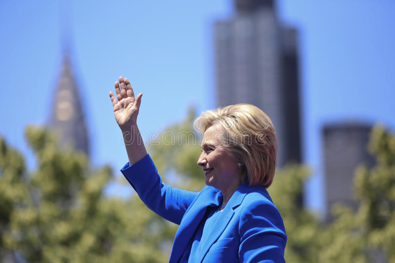 Hillary Clinton announces candidacy. Hillary Clinton in profile waving lighted by direct sun with foliage and the Chrysler Building in the background royalty free stock image