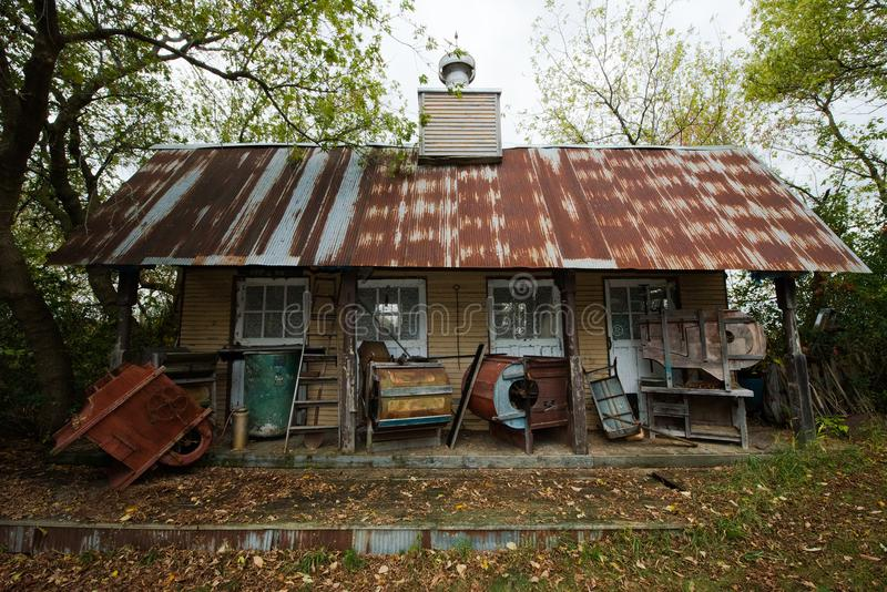 Hillbilly Redneck Mountain Shack, Cabin. Scene of a hillbilly or redneck shack, house, home, or cabin out in the mountains or hills. Old antique junk and trash stock photos