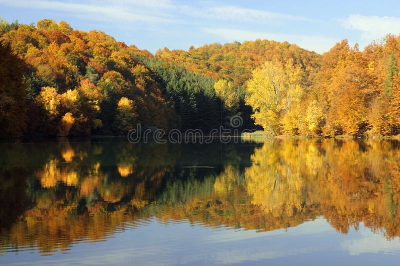 Hills of autumn colors reflected in a calm lake stock image