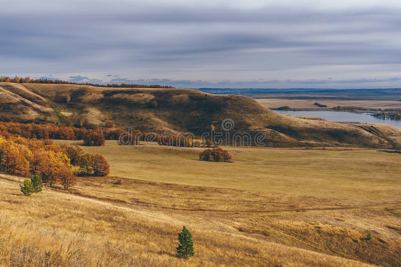 Hills with autumnal forest. Hills and fields with autumnal forest and lake stock image