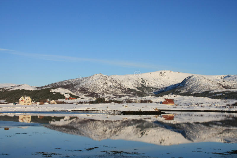 Hills and houses mirroring in a Lofoten's fjord. The small village of mirroring in Mortsund's fjord stock photos