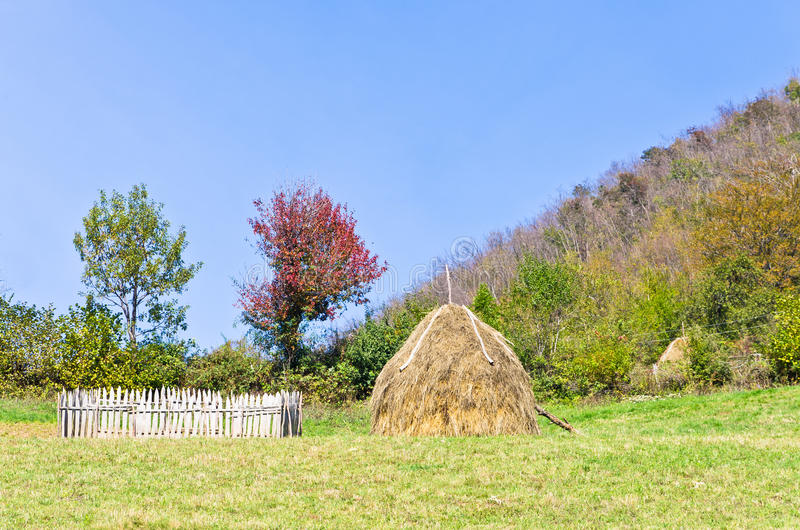 Hills on mount Bobija, small wooden fence, haystack and colorful trees. West Serbia stock images