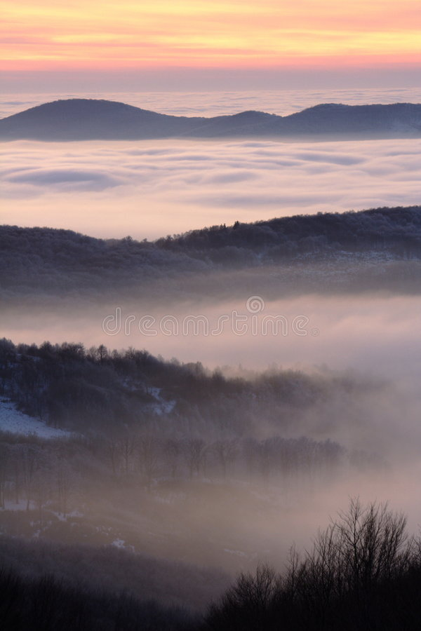 Hills over clouds at sunset royalty free stock photography