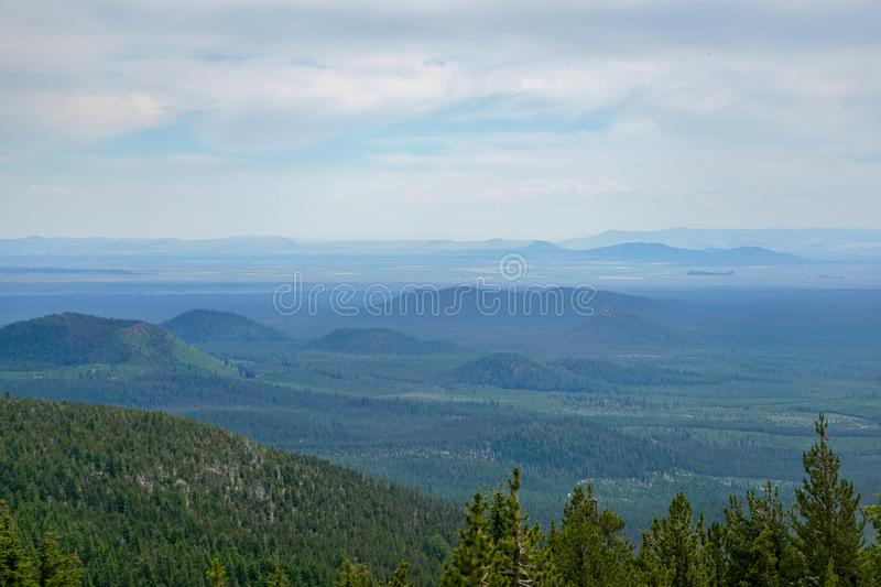 Hills and Valleys. A view of hills and valleys. Looking down from above the tree line. Paulina Peak, Oregon. Distant mountains and an expansive sky royalty free stock photography