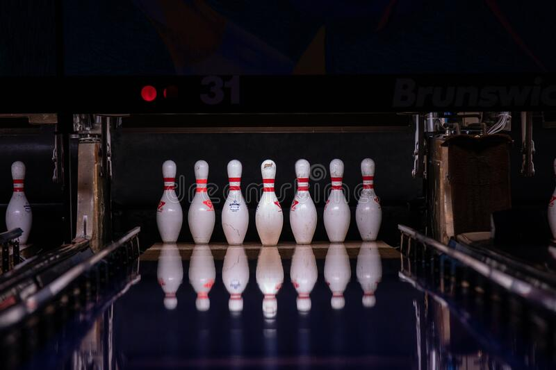 Bowling pins at the end of a bowling alley reflecting on a polished lane floor. Hillsboro, Oregon \ USA - March 16 2019: Bowling pins at the end of a bowling royalty free stock photography