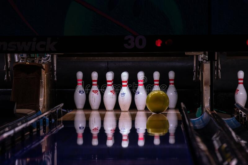Yellow bowling ball is about to hit  pins at the end of a bowling alley. Hillsboro, Oregon  USA - March 16 2019: Yellow bowling ball is about to hit  pins at the stock photo