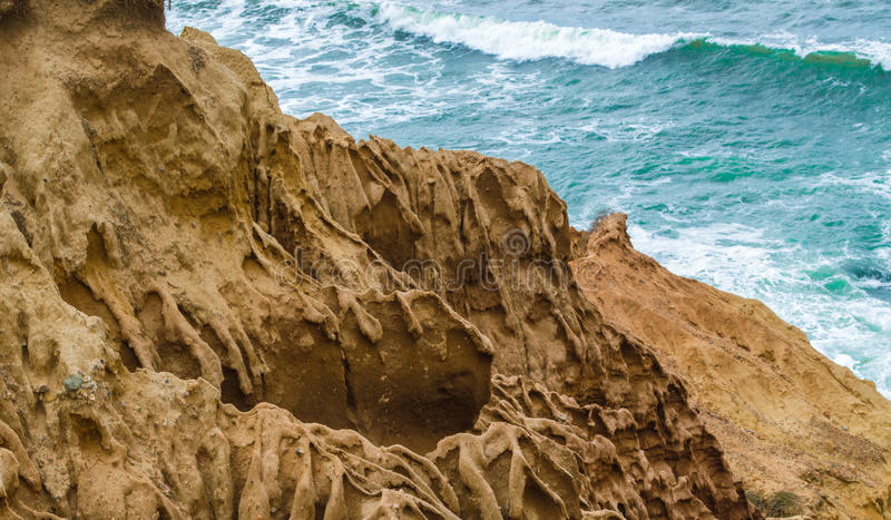 Hillside cliffs of flowing sand at the Pacific ocean. Jagged hillside cliffs of flowing sand overlooking the Pacific ocean at Point Loma in San Diego, California royalty free stock photo