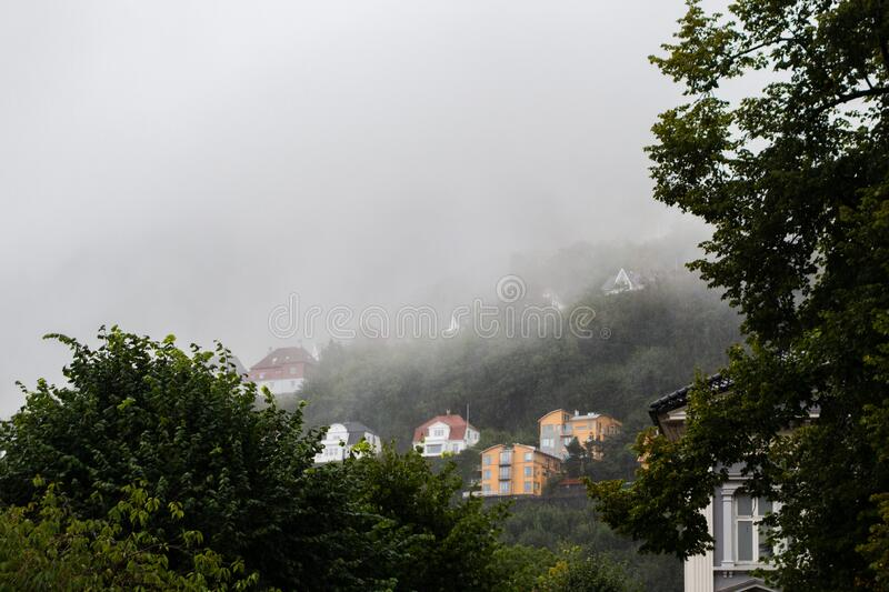 Hillside homes at Floyfjellet on a rainy and foggy autumn day in Bergen Norway royalty free stock image