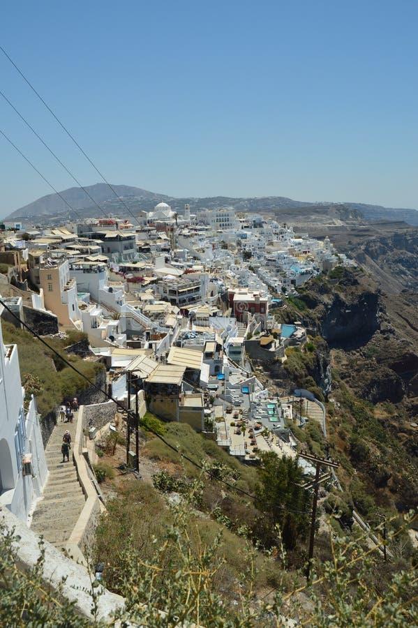 Hillside infini complètement des Chambres blanches et bleues typiques dans la belle ville de Fira sur l'île de Santorini Architec images stock