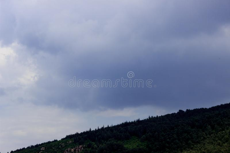 Hillside on mountain and dark cloudy sky landscape. Green forest hillside on mountain and dark blue cloudy sky landscape royalty free stock photo