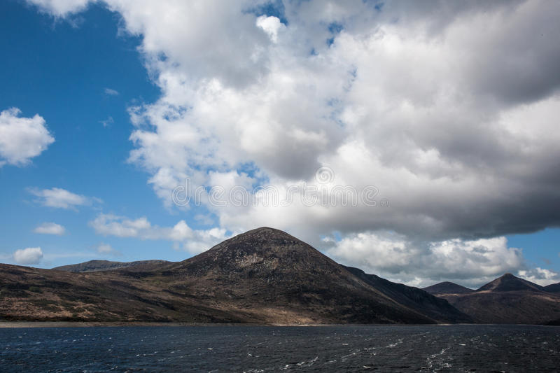 Hillside in Silent Valley, County Down, Northern Ireland. Hills along shores of lake in Silent Valley, County Down, Northern Ireland with white clouds in blue royalty free stock images
