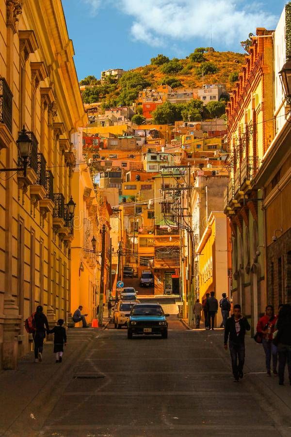 Hillside street view with bright blue car stock photography
