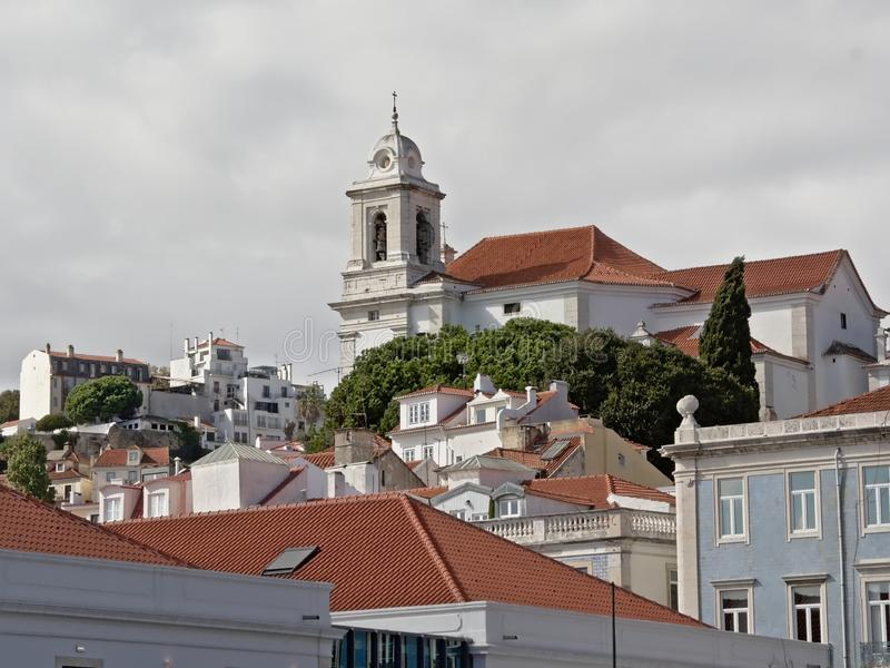 Hilltop in alfama district with church of Saint Stephen and traditional portuguese houses. Hilltop in alfama district with bell tower of the catholic church in stock photo