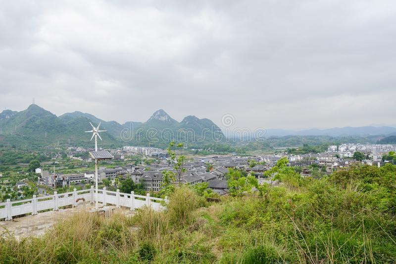 Hilltop balustraded platform overlooking Qingyan town in cloudy. Balustraded platform with wind generator and solar battery on weedy hilltop overlooking Qingyan royalty free stock photo