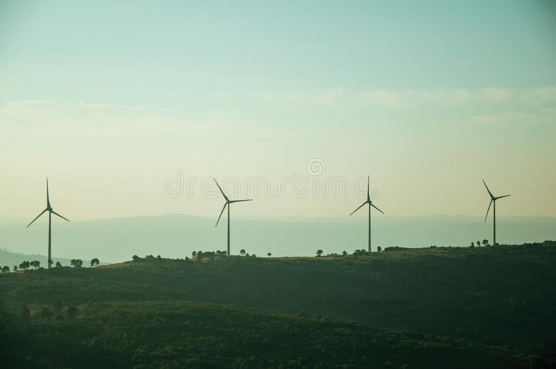 Hilly landscape with wind turbines on sunset. Hilly landscape covered by trees and several wind turbines for electric power generation, on sunset at Guarda. This stock photography