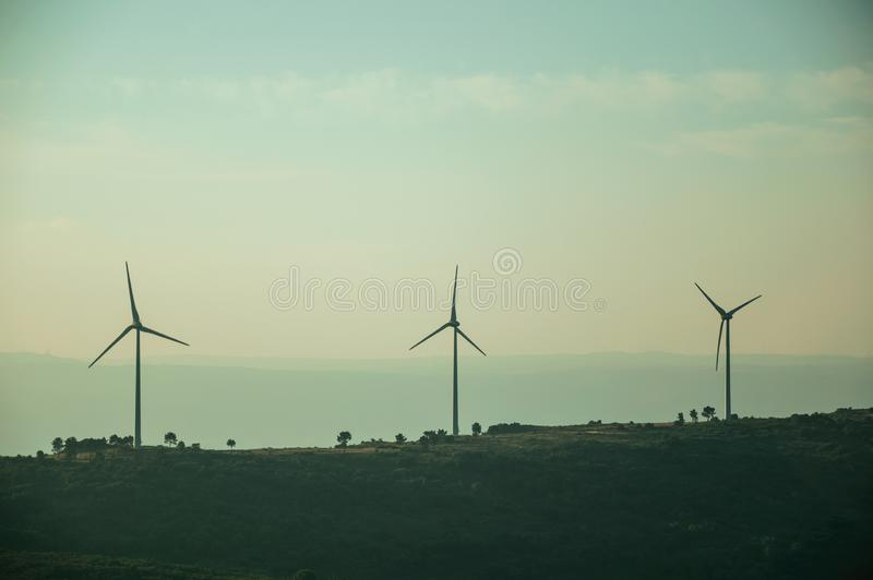 Hilly landscape with wind turbines on sunset. Hilly landscape covered by trees and several wind turbines for electric power generation, on sunset at Guarda. This stock photos