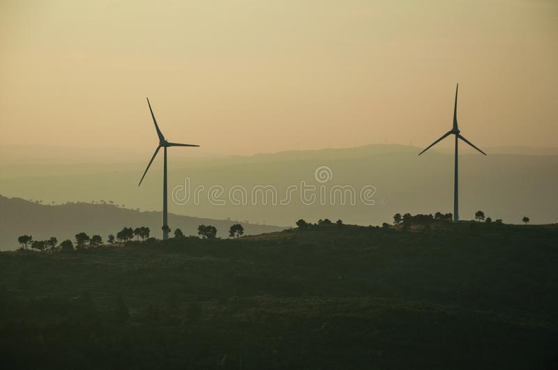 Hilly landscape with wind turbines on sunset. Hilly landscape covered by trees and several wind turbines for electric power generation, on sunset at Guarda. This royalty free stock photography
