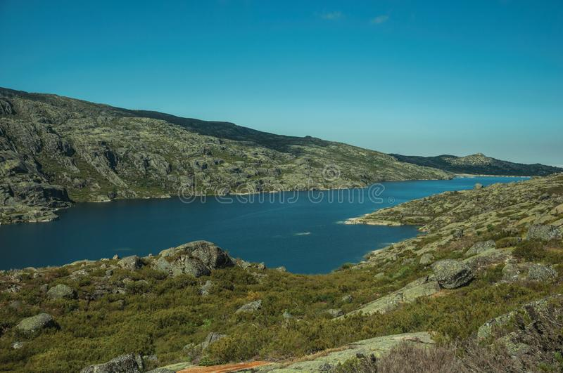 Hilly landscape with lake on highlands. Hilly landscape covered by bushes and rocks with the Long Lake on highlands, in a sunny day at the Serra da Estrela. The stock images