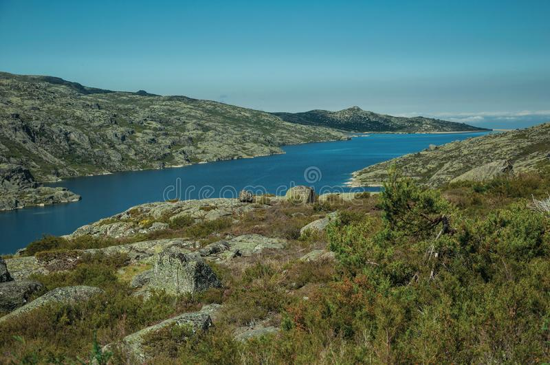 Hilly landscape with lake on highlands. Hilly landscape covered by bushes and rocks with the Long Lake on highlands, in a sunny day at the Serra da Estrela. The stock image