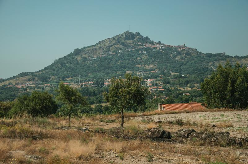 Hilly landscape with the small Monsanto village on top. Hilly landscape covered by trees and rocks in a sunny day, with the small Monsanto village on top of it royalty free stock photo