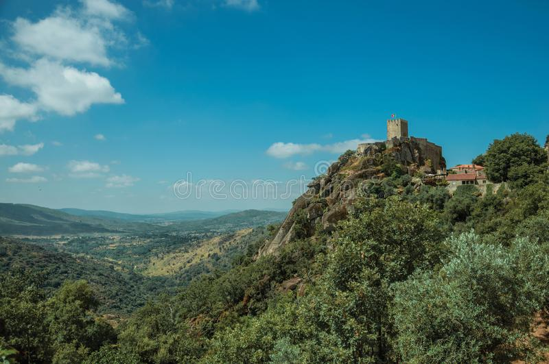 Hilly landscape with tower of castle over rocky cliff. Hilly landscape with stone walls and tower of Castle over rocky cliff covered by trees, in a sunny day at royalty free stock photography