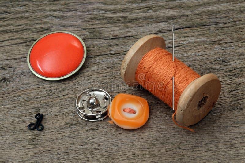 Hilo, botones, gancho y aguja en una tabla de madera imagenes de archivo