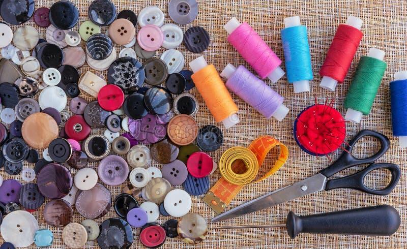 Hilos de coser, botones para la ropa y otros accesorios para coser y la costura ?oncept de accesorios de costura imagenes de archivo